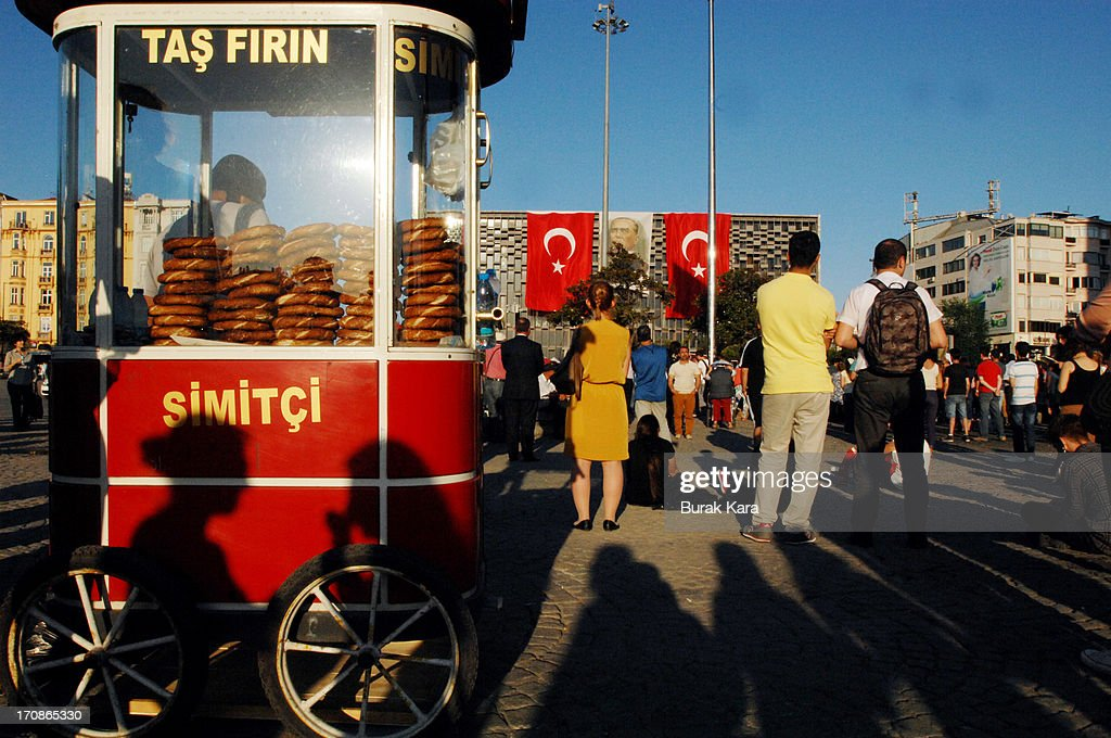 People stand near a traditional Turkish sesamed bagel vendor during a silent protest in Taksim Square June 19, 2013 in Istanbul, Turkey. Performance artist Erdem Gunduz, nicknamed 'The Standing Man,' became a new symbol of the anti-government protests after a eight-hour vigil in Taksim Square. Gunduz reportedly said he was protesting in solidarity with demonstrators after they were evicted from Gezi Park that adjoins Taksim Square. The protests began in May, with environmentalists upset over plans to build in Gezi Park, and has grown into a broader demonstration against Prime Minister Tayyip Erdogan's government.