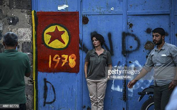 People stand near by the Kurdistan Workers Party flag in the center of Diyarbakir on September 14 2015 Following an explosion and gunfire late...