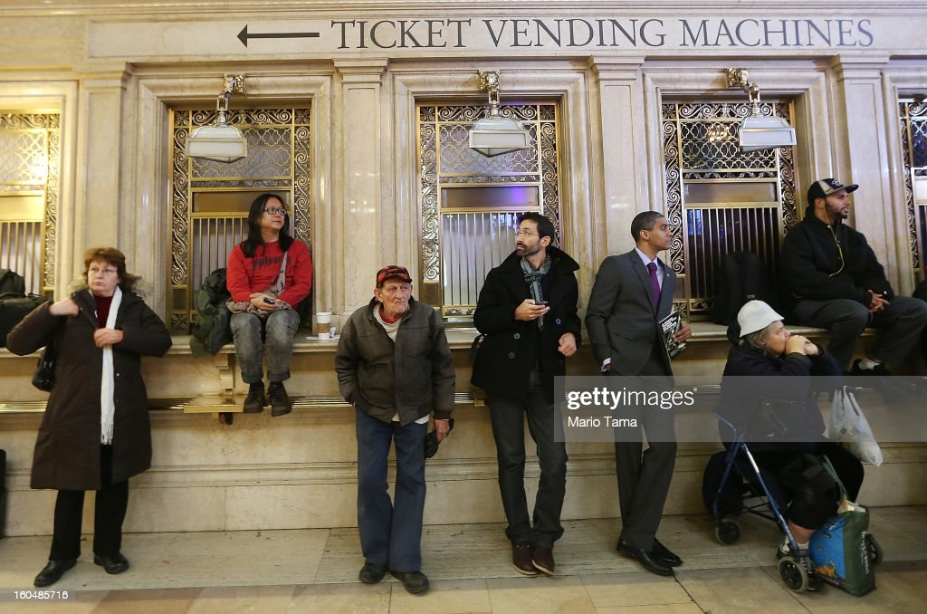 People stand near closed ticket windows in Grand Central Terminal during centennial celebrations on the day the famed Manhattan transit hub turns 100 years old on February 1, 2013 in New York City. The terminal opened in 1913 and is the world's largest terminal covering 49 acres with 33 miles of track. Each day 700,000 people pass through the terminal where Metro-Noth Railroad operates 700 trains per day.