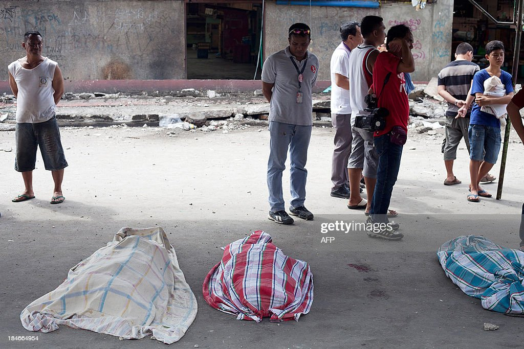 People stand near covered victim's bodies in Cebu City, Philippines after a major 7.1 magnitude earthquake struck the region on October 15, 2013. At least 20 people were killed on October 15 when the earthquake tore down buildings across three islands that are among the Philippines' most popular tourist attractions, authorities said. AFP PHOTO / Chester Baldicantos