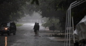 People stand near downed branches as Tropical Storm Isaac begins to move ashore on August 26 2012 in Marathon Florida According to reports Isaac has...