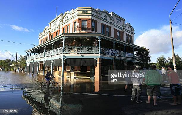 People stand near flood waters next to the Winsome Hotel which remained open for patrons in Lismore on May 22 2009 A second Australian state was...