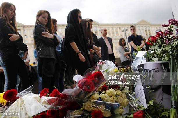 TOPSHOT People stand near flowers laid in memory of Linkin Park frontman Chester Bennington in front of the US embassy in central Moscow on July 22...