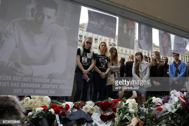 People stand near flowers laid in memory of Linkin Park frontman Chester Bennington in front of the US embassy in central Moscow on July 22 2017...