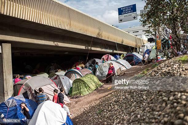 People stand near tents in an illegal campsite of Albanian asylum seekers situated under the A6 motorway's Kitchener bridge next to the entrance of...