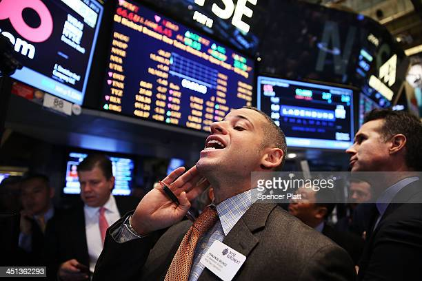 People stand near the broker's booth for 500com Limited as it's IPO is set on the floor of the New York Stock Exchange on November 22 2013 in New...
