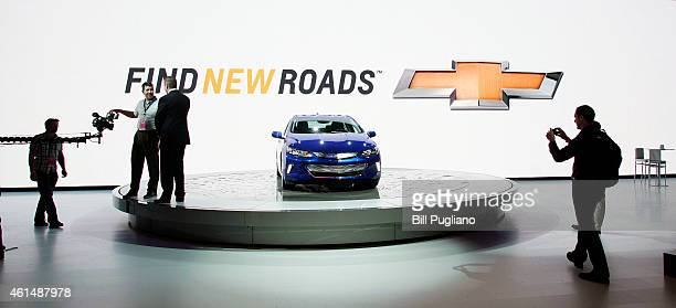 People stand near the Chevrolet Volt display at the 2015 North American International Auto Show on January 13 2015 in Detroit Michigan More than 5000...