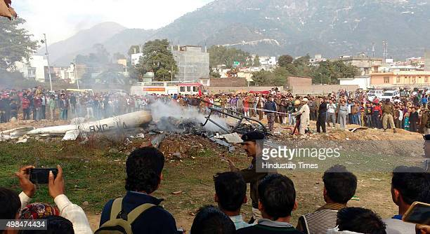 People stand near the remains of a private helicopter as rescue personnel douse the smoldering wreckage of crashed helicopter at Katra on November 23...
