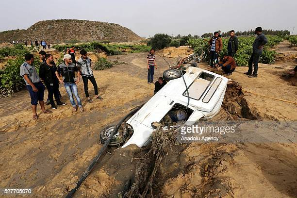 People stand next to a car sunk into a land filled with waste water as a pool belongs to waste water purification plant cracks up and causes damage...