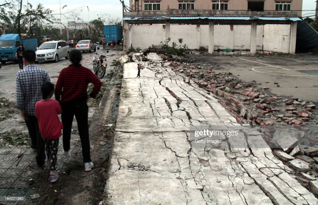 People stand next to a collapsed wall on March 20, 2013 in Dongguan, China. Nine people have been killed and about 272 others injured after a thundersand hailstorm swept Dongguan city on Wednesday afternoon.