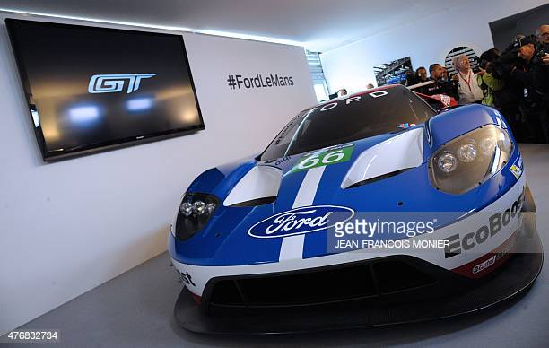 People stand next to a Ford GT after a press conference before the 83rd Le Mans 24hours endurance race on June 12 2015 in Le Mans western France The...