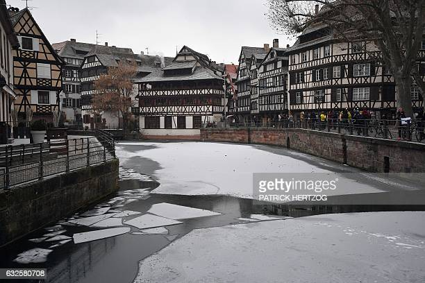 People stand next to a frozen river the Ill on January 24 2017 in the 'Petite France' district in central Strasbourg eastern France A toxic cocktail...