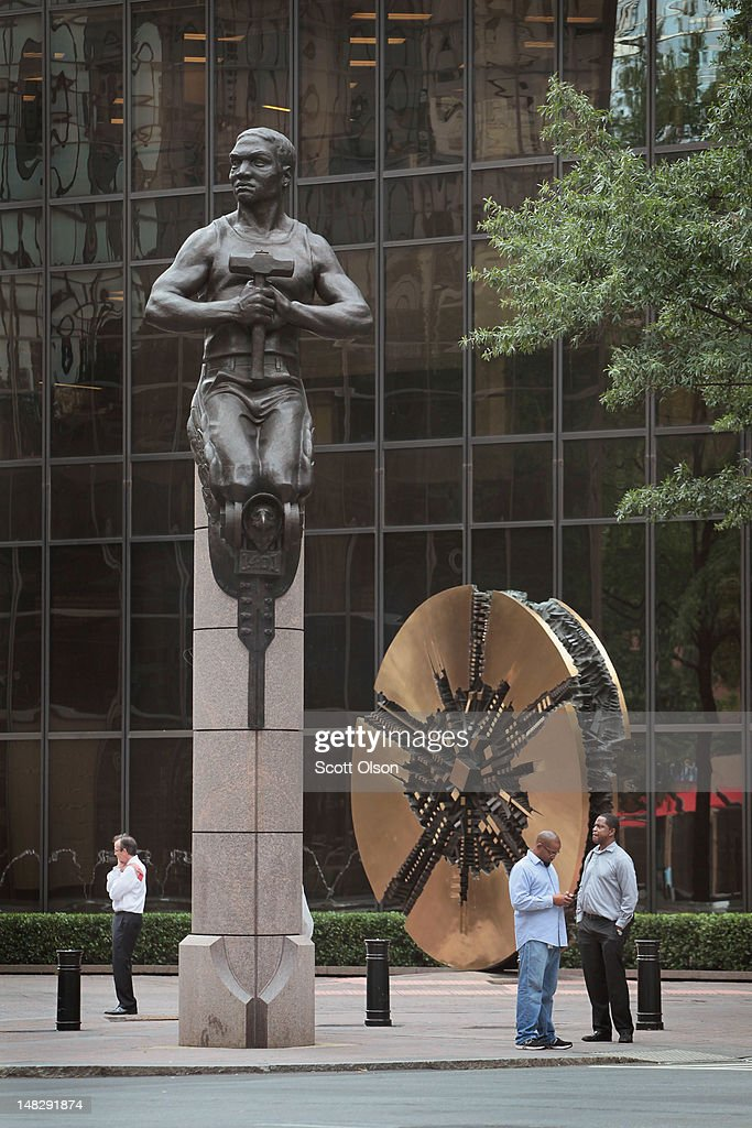 People stand next to a sculpture representing transportation in Independence Square July 11, 2012 in Charlotte, North Carolina. The sculpture is one of four located at each street corner at the square depicting transportation, industry, commerce, and future. Businesses and attractions in Charlotte are anticipating a boost in visitors when the city hosts the 2012 Democratic National Convention (DNC) September 3-6.