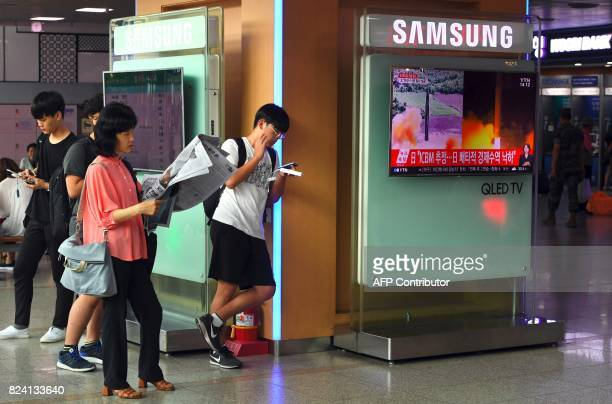 People stand next to a television screen showing a video footage of North Korea's tests launch of intercontinental ballistic missiles at a railway...