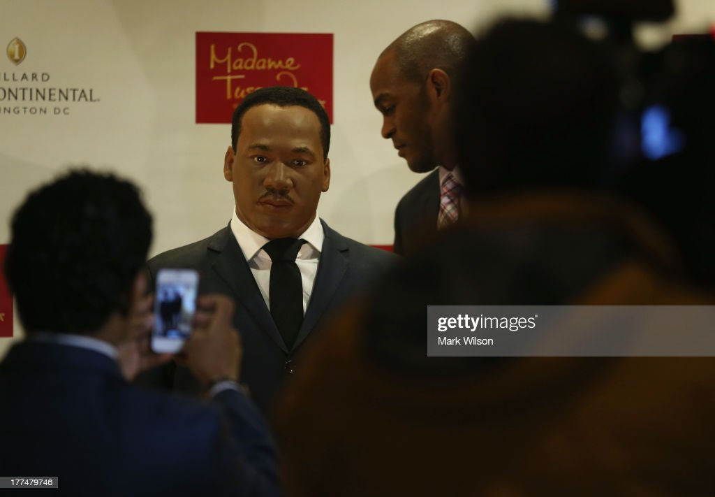 People stand next to a wax figure of Rev. Martin Luther King Jr. that is on display at the Willard Intercontinental Hotel August 23, 2013 in Washington, DC. The wax figure is on loan from Madame Tussauds to help commemorate the 50th anniversary of the March on Washington.