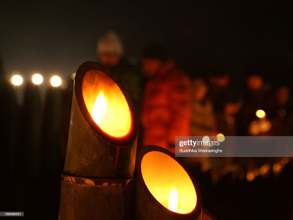 People stand next to bamboo lanterns and pray for victims of the 1995 'Great Hanshin earthquake' during a memorial ceremony on January 17, 2013 in Kobe, Japan. Memorial services were held to mark the 18th anniversary of the 1995 massive earthquake, hundreds of people gathered early this morning to pay their respects and light bamboo lanterns in the park for more than 6,400 people who lost their lives in the 7.3 magnitude earthquake.
