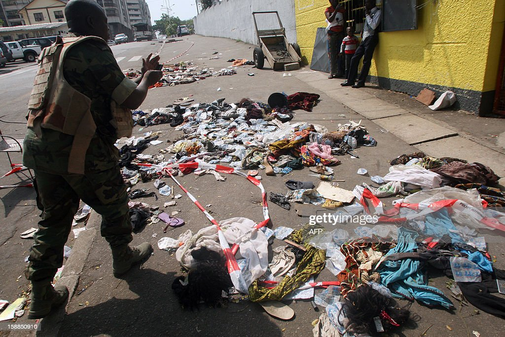 People stand next to clothing and various items spread over the pavement at the scene following a stampede in Abidjan, on January 1, 2013. At least 60 people died and at least dozens were injured as crowds stampeded overnight during celebratory New Year's fireworks, Ivory Coast rescue workers said on January 1, 2013.