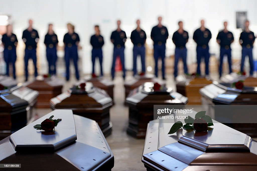 People stand next to Coffins of victims in a hangar of the Lampedusa airport on October 5, 2013 after a boat with migrants sank, killing more than hundred people. Italy mourned today the 300 African asylum-seekers feared dead in the worst ever Mediterranean refugee disaster, as the government appealed for Europe to stem the influx of migrants. Italian emergency services hoped to resume the search for bodies despite rough seas after the accident, in which 111 African asylum-seekers are confirmed dead and around 200 more are still missing.
