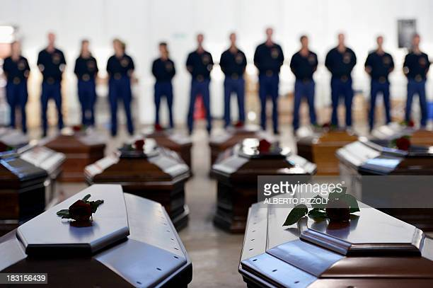 People stand next to Coffins of victims in a hangar of the Lampedusa airport on October 5 2013 after a boat with migrants sank killing more than...