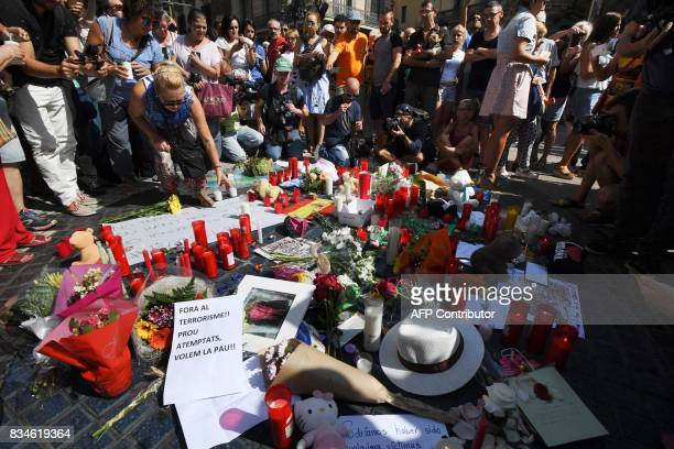 People stand next to flowers candles a sign reading ' Out terrorism and attacks we want peace' and other items set up on the Las Ramblas boulevard in...