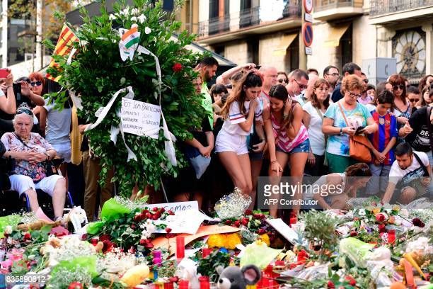 People stand next to flowers candles and other items set up on the Las Ramblas boulevard in Barcelona as they pay tribute to the victims of the...