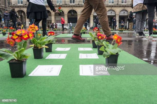 People stand next to flowers laid by members of the group 'les Morts de la Rue' on the Place du Palais Royal in Paris on March 21 in memory of 501...