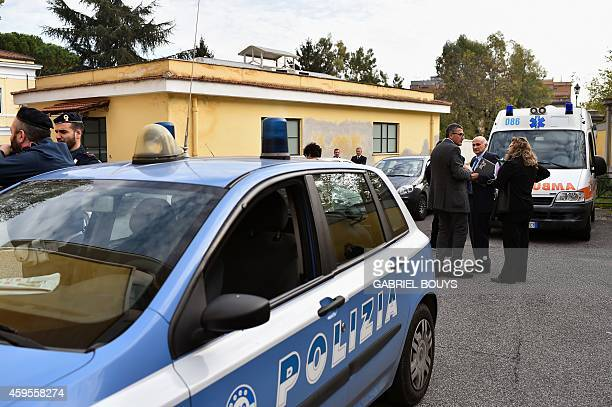 People stand next to police cars at the main entrance of the Lazzaro Spallanzani Institute in Rome on November 25 2014 A doctor 50years old from...