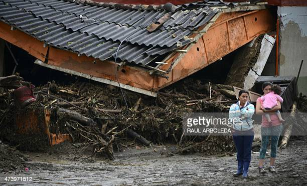 People stand next to rubble after a landslide in Salgar Municipality Antioquia department Colombia on May 19 2015 A massive landslide tore through a...