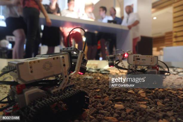 People stand next to small replicas of the NASA's Mars Exploration Rover during the Sunny Side of the Doc 2017 an international market dedicated to...