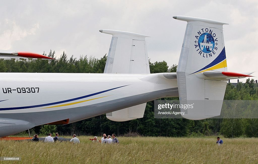 People stand next to the aircraft 'AN-22' ('Antaeus') during a demonstration flight from the airfield 'Svyatoshin' (Kiev) to the airport 'Kyiv-Antonov' (Hostomel) in Kiev, Ukraine on May 30, 2016. Ukrainian aircraft 'AN-22' is restored on the aircraft factory 'Antonov' and returned to commercial operation. The 'AN-22' is the world's first wide-body transport plane and the world's largest turbo-prop airplane.