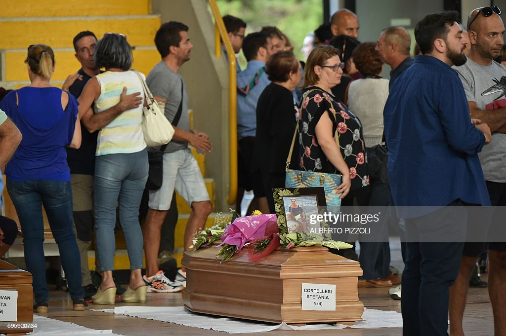 People stand next to the coffins of earthquake victims in a gymnasium arranged in a chapel of rest on August 26 in Ascoli Piceno two day after a...