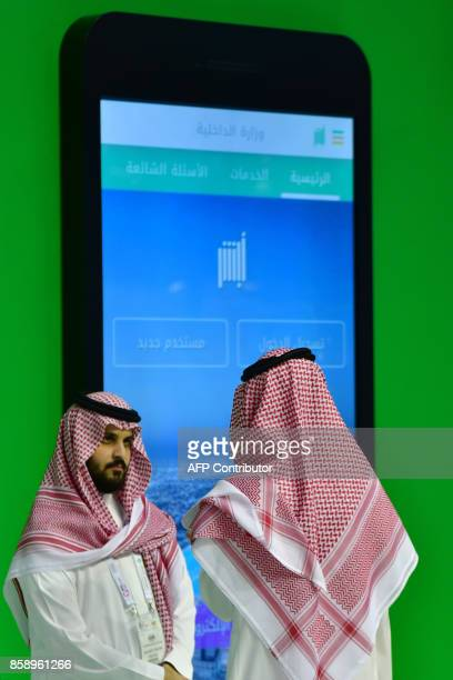 People stand next to the Ruyaa 2030 pavilion at the Gitex 2017 exhibition at the Dubai World Trade Center in Dubai on October 8 2017 / AFP PHOTO /...