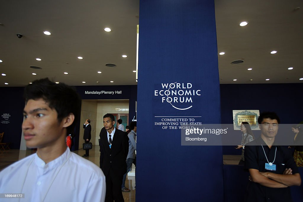 People stand next to the World Economic Forum (WEF) logo displayed in front of the plenary hall at the Myanmar International Convention Center ahead of the World Economic Forum on East Asia in Naypyidaw, Myanmar, on Wednesday, June 5, 2013. Myanmar hosts the three-day World Economic Forum on East Asia starting today, with heads of state and executives from companies including General Electric Co., Coca-Cola Co. and WPP Plc attending. Photographer: Dario Pignatelli/Bloomberg via Getty Images