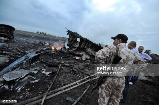 People stand next to the wreckages of the malaysian airliner carrying 295 people from Amsterdam to Kuala Lumpur after it crashed near the town of...