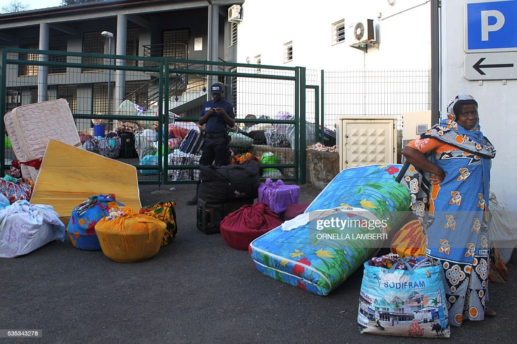 People stand next to their belongings before getting into a bus on May 29, 2016 in Ouangani, center part of the French overseas region and department Mayotte, to go to the capital, Mamoutzou. Around 500 'illegal immigants', mostly from Comoros, evicted from their house by local Mayotte inhabitants, camp out since May 15, 2016 on Republique square at Mamoudzou as associations try to rehouse them. Rising anti-migrant anger has seen groups of up to 100 men gather in villages with lists of houses belonging to foreigners and going from door to door forcing them to leave. Police have tried to prevent violence, but have been unable to stop the pressure mounting on foreigners -- including many who are living on Mayotte legally -- who have fled their homes in fear. Mayotte opted to remain under French rule when the other islands in the Comoros archipelago chose independence in 1975. / AFP / ORNELLA