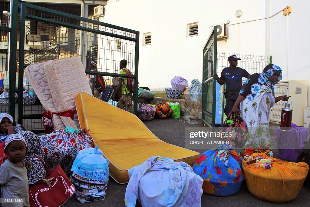 People stand next to their belongings on May 29, 2016 in Ouangani, center part of the French overseas region and department Mayotte, before travelling to the capital, Mamoutzou. Around 500 'illegal immigants', mostly from Comoros, evicted from their house by local Mayotte inhabitants, camp out since May 15, 2016 on Republique square at Mamoudzou as associations try to rehouse them. Rising anti-migrant anger has seen groups of up to 100 men gather in villages with lists of houses belonging to foreigners and going from door to door forcing them to leave. Police have tried to prevent violence, but have been unable to stop the pressure mounting on foreigners -- including many who are living on Mayotte legally -- who have fled their homes in fear. Mayotte opted to remain under French rule when the other islands in the Comoros archipelago chose independence in 1975. / AFP / ORNELLA