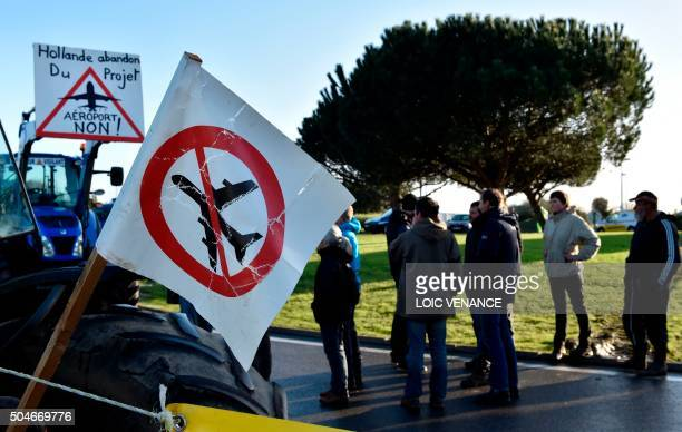 People stand next to tractors blocking a traffic circle access to the SaintNazaire bridge on January 12 2016 in SaintNazaire western France during a...