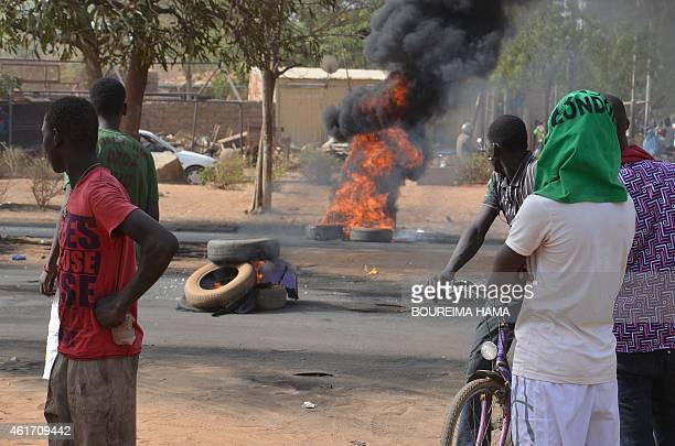 People stand next to tyres set on fire in Niamey on January 18 2015 after police fired teargas to disperse a banned opposition demonstration in the...