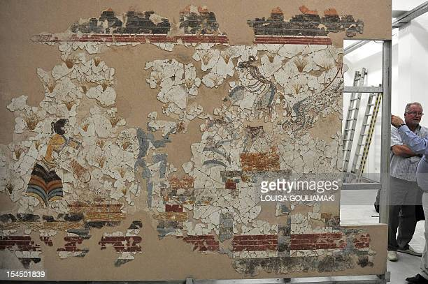 People stand next to wall paintings preserved from one of Greece's most famous archaeological sites the prehistoric town of Akrotiri on the island of...