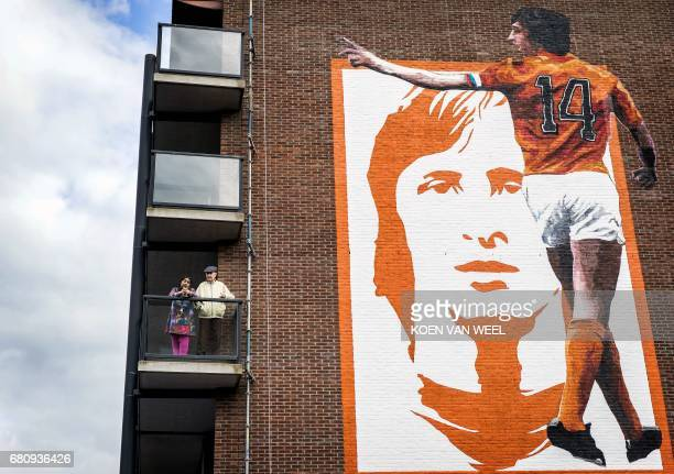People stand on a balcony as a giant picture of former Dutch professional football player and coach Johan Cruyff made by Brazilian artist Paulo...