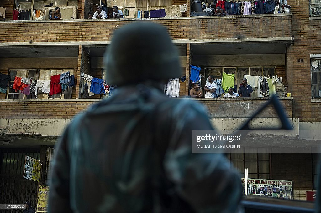 People stand on a balcony as South African Police officers supported by soldiers of the South African Defence Force SADF patrol in Hilbrow...