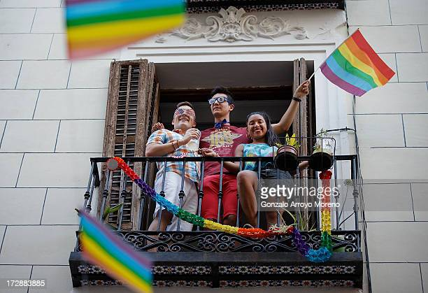 People stand on a balcony with gay pride flag in Chueca neigborhood during the Madrid Gay Pride Festival 2013 on July 4 2013 in Madrid Spain...