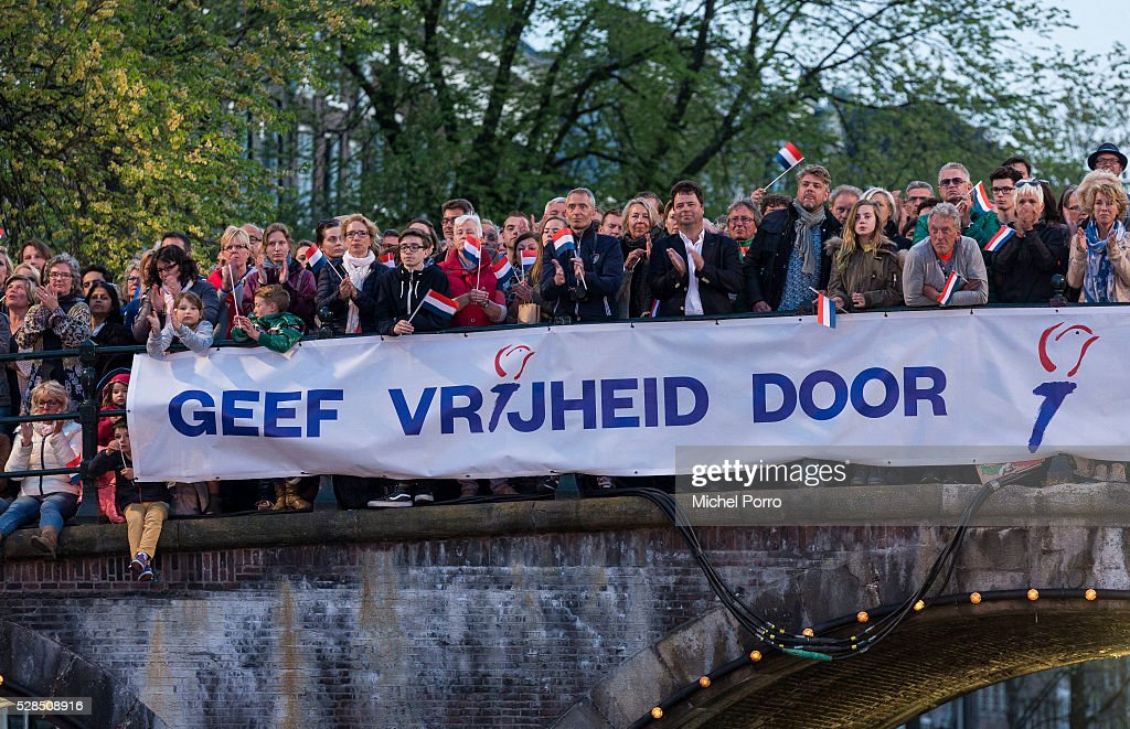 People stand on a bridge which displays a banner reading 'Pass On Freedom' watch the Liberation Day Concert on May 5, 2016 in Amsterdam, Netherlands. Liberation Day (Dutch: Bevrijdingsdag) is celebrated each year on May the 5th to mark the end of the occupation by Nazi Germany during World War II.