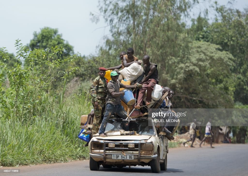 People stand on a car with their belongings on the road from Mbaiki to Bangui on April 8, 2014. The crisis in the strife-torn Central African Republic has left 1.6 million people -- a third of the population -- in urgent need of food, the United Nations said Monday. Thousands of people have been killed in a wave of sectarian violence across the Central African Republic that has lasted for more than a year, despite the presence of African Union and French peacekeeping troops. AFP PHOTO / MIGUEL MEDINA