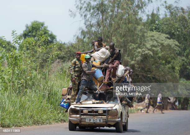 People stand on a car with their belongings on the road from Mbaiki to Bangui on April 8 2014 The crisis in the strifetorn Central African Republic...