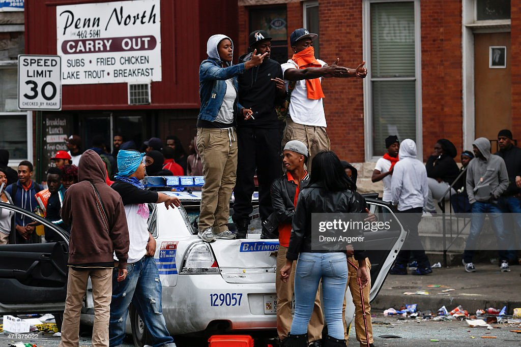 People stand on a damaged Baltimore Police car near the intersection of Pennsylvania Avenue and North Avenue April 27 2015 in Baltimore Maryland...