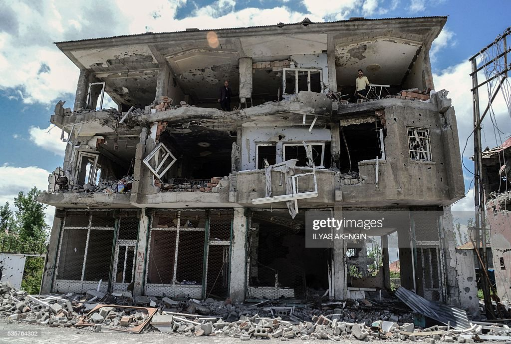 People stand on a damaged building after heavy fightings between Turkish government troops and Kurdish fighters after the curfew in the southeastern Turkey Kurdish town of Yuksekova, near the border with Iraq and Iran, on May 30, 2016. / AFP / ILYAS