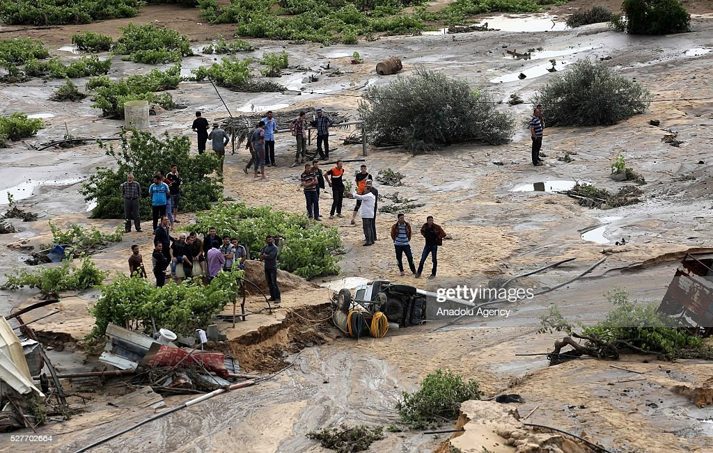 People stand on a land filled with waste water as a pool belongs to waste water purification plant cracks up and causes damage on the area in Ez-Zeytun neighborhood of Gaza City, Gaza on May 3, 2016.