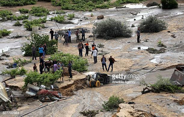 People stand on a land filled with waste water as a pool belongs to waste water purification plant cracks up and causes damage on the area in...
