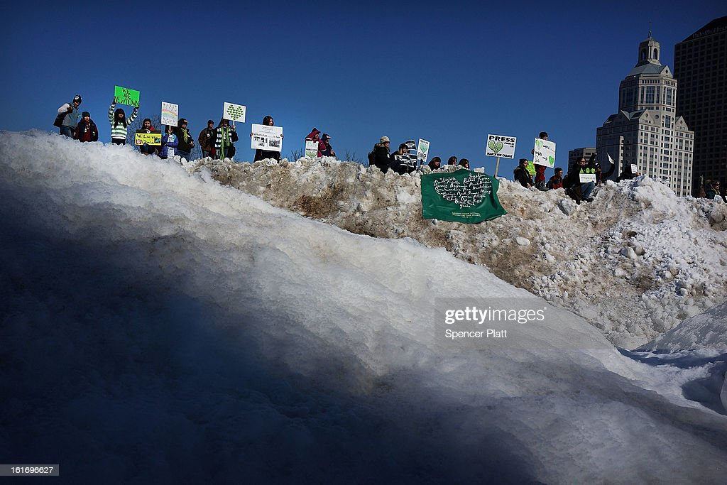 People stand on a mound of snow holding signs during a rally at the Connecticut State Capital to promote gun control legislation in the wake of the December 14, 2012, school shooting in Newtown on February 14, 2013 in Hartford, Connecticut. Referred to as the 'March for Change' and held on the two-month anniversary of the massacre in Newtown, Connecticut, participants called for improved gun safety laws. Among the safety measures being demanded are for universal background checks, more work within the mental health community and restricting high-capacity magazines.